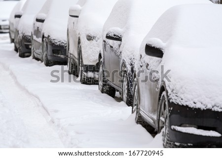Parked cars after winter blizzard - stock photo