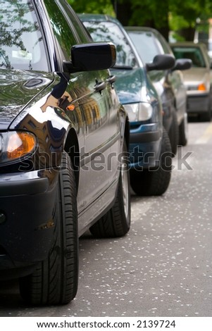 parked cars and cherry tree petals on the road - stock photo