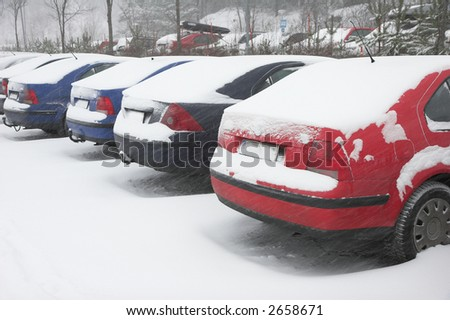 parked cars covered in snow during snowstorm - stock photo