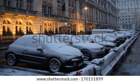parked cars covered with snow, in a cold winter in London