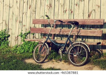 Parked old bicycle near a bench in a summer sunny day