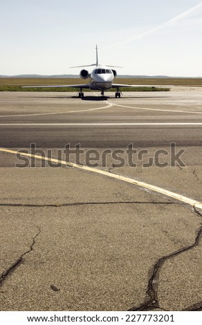 parked private airplane on the runway. white civic jet - stock photo