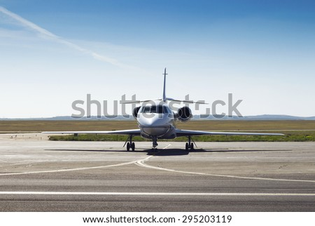 parked private airplane on the runway. white civic, modern jet - stock photo