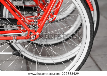 Parked red street bicycles for rent, rear wheels fragment, selective focus with shallow DOF - stock photo
