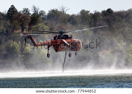 PARKER CANYON LAKE, ARIZONA, USA - MAY 24: An Erickson S-64 Aircrane helicopter fills its tank from a Lake while fighting a nearby brush fire on May 24, 2011 in Parker Canyon Lake, Arizona, USA. - stock photo