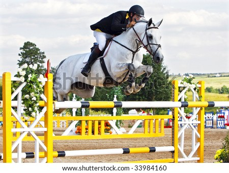 PARKER, CO - JULY 18: Mexican Olympian Antonio Maurer jumps Valentina to third place in the $50,000 Grand Prix of Denver at the Colorado Horse Park on July 18, 2009 in Parker, CO. - stock photo