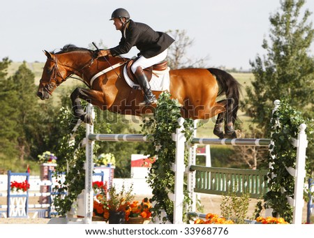 PARKER, CO - JULY 18: Mexican Olympian Antonio Maurer rides Callao to a fourth-place finish in the $50,000 Grand Prix of Denver at the Colorado Horse Park on July 18, 2009 in Parker, CO. - stock photo