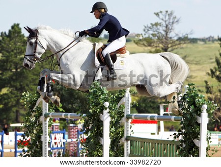 PARKER, CO - JULY 18: Successful Canadian rider Karen Cudmore guides Ceonto to a top-five finish in the $50,000 Grand Prix of Denver at the Colorado Horse Park on July 18, 2009 in Parker, CO. - stock photo