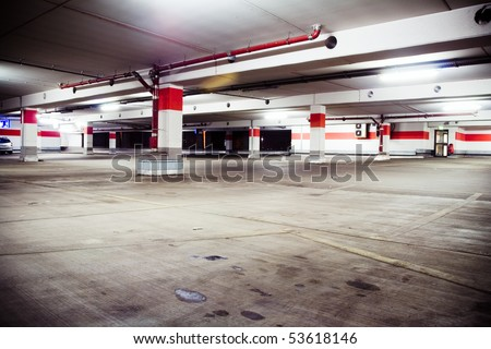 Parking garage, grunge and dirty underground interior. Neon light in bright industrial building. - stock photo