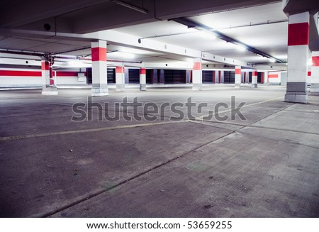 Parking garage, grunge underground interior. Neon light in bright industrial building.
