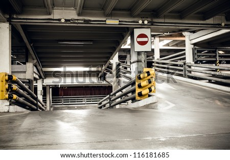 Parking garage in basement, underground interior and stop sign, construction technology steel and concrete Neon light in bright industrial building. - stock photo