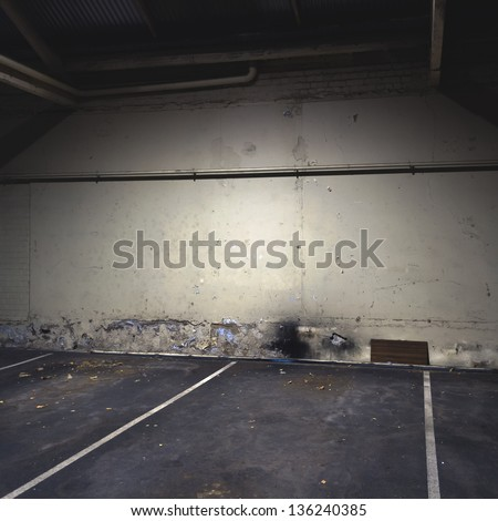 Parking garage interior at night with empty bays and distressed wall texture. - stock photo