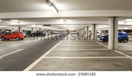Parking garage - interior shot of multi-story car park - stock photo