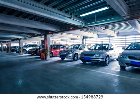 Parking garage, interior with a few parked cars.  - stock photo