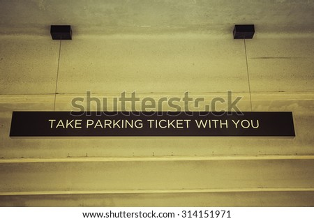 Parking garage ticket sign from low angle - vintage colors - stock photo