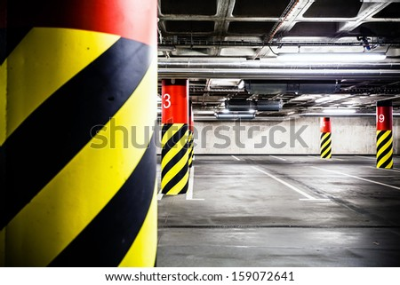 Parking garage underground industrial interior. Concrete grunge industrial parking lot and column with warning sign, modern industry interior.