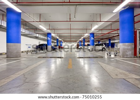 Parking garage, underground interior with a few parked cars - stock photo