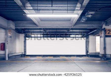 Parking garage underground interior with blank billboard - stock photo