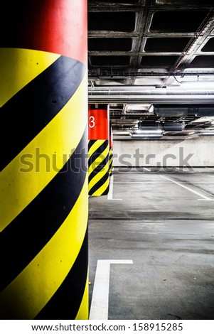 Parking garage underground modern interior. Concrete grunge industrial parking lot and column with warning sign, industrial interior.