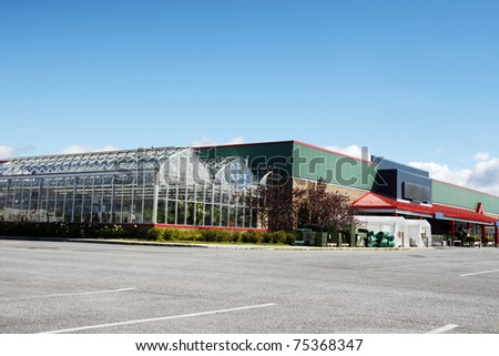 Parking lot view of a hardware store with greenhouse nursery attached to it - stock photo