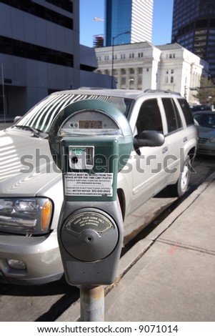 Parking meter in front of silver vehicle in downtown area.