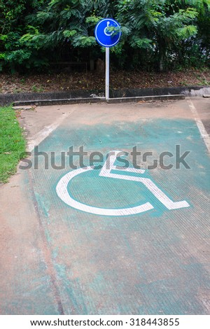 parking space reserved handicapped on road with disabled sign - stock photo