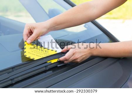 Parking ticket placed under windshield wiper - stock photo