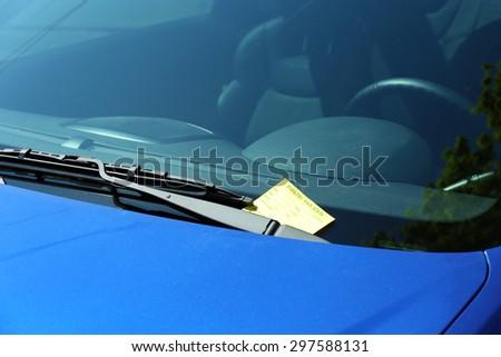 Parking violation ticket on car windshield, closeup - stock photo