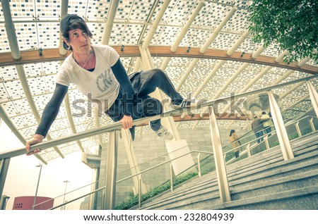 Parkour athlete jumping over a handrail - Free runner performing tricks in a urban settlement - Parkour,free running,youth,sport and lifestyle concept - stock photo