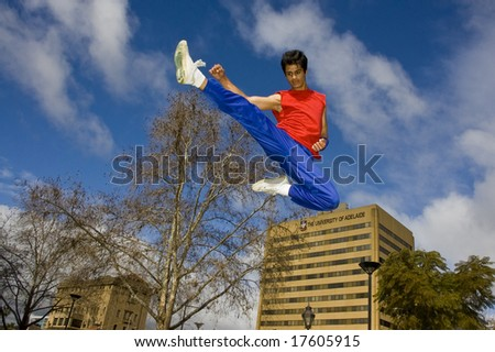 Parkour jumper jumps off block with big kick - stock photo