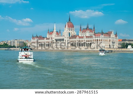 Parliament building in Budapest, Hungary on a bright sunny day with two passenger ships - stock photo