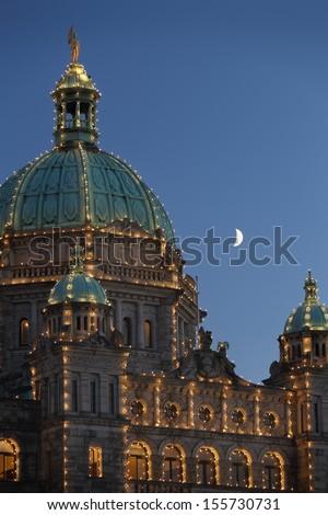 Parliament Building Moon, Victoria, BC. The crescent moon rises beside the parliament buildings in Victoria. British Columbia, Canada.  - stock photo