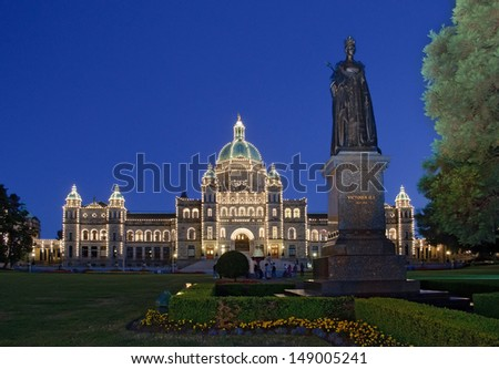 parliament of BC in Victoria with old statue of Queen Victoria lit up at dusk - stock photo