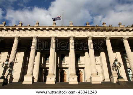 Parliament of Victoria in Melbourne, Australia. Flag is halfway up the pole in memory of famous 2009 bushfire victims. - stock photo