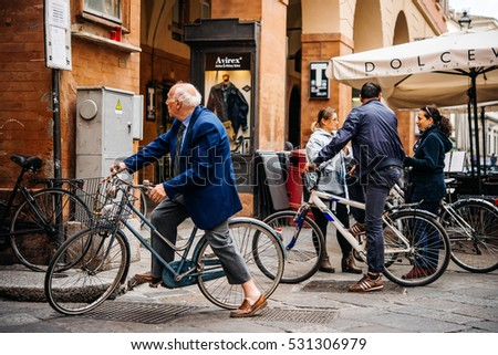 PARMA, ITALY - APRIL 22, 2016: People ride bicycles in the old city of Parma, Emilia Romagna region, Italy.