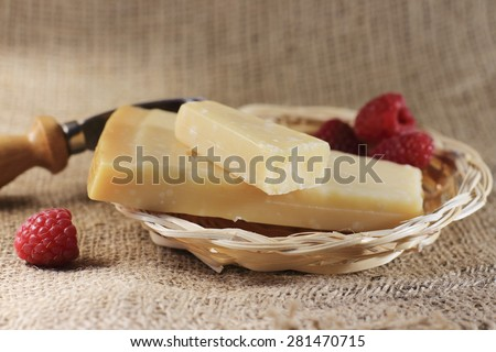 Parmesan cheese and slice in a basket, special little knife for parmesan,on natural jute tablecloth - stock photo
