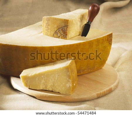 parmesan cheese on a wooden table with knife - stock photo