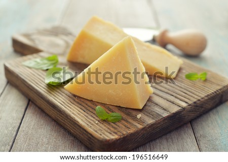 Parmesan cheese on cutting board with basil and knife on wooden background - stock photo