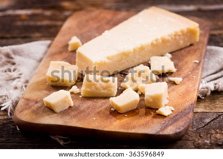 parmesan cheese on old wooden board - stock photo