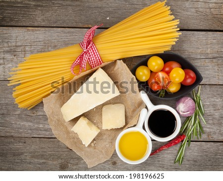 Parmesan cheese, pasta, tomatoes, vinegar, olive oil, herbs and spices on wooden table background - stock photo