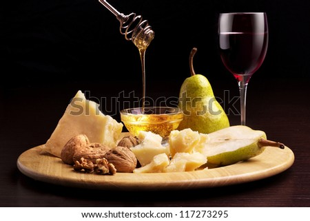 parmesan cheese, pears, honey, walnuts and wineglass - stock photo