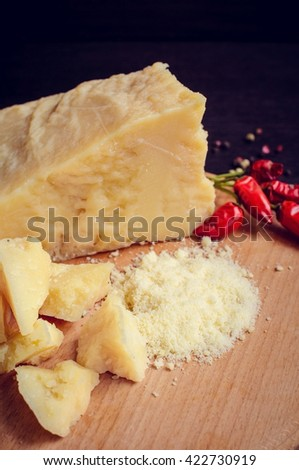 Parmesan cheese with chili pepper on wooden chopping board on dark background. Grated parmesan. Pieces of parmesan. Tasty appetizers. Cheese platter. Cheese board. Cheese slice. Selective focus. - stock photo