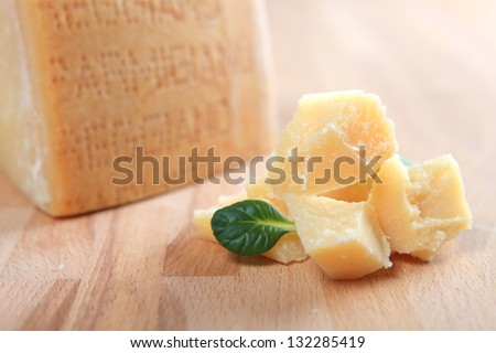 Parmesan cheese with fresh basil leaves on wooden table - stock photo