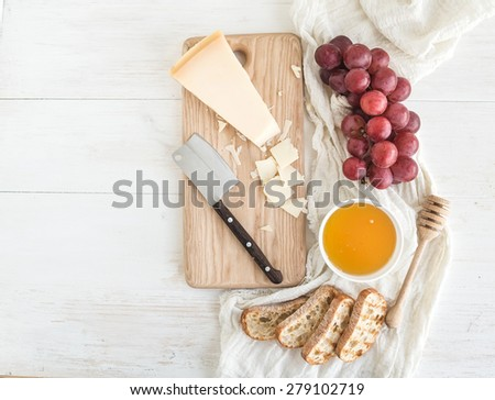 Parmesan cheese with grapes, honey and bread slices on wooden chopping board over rustic white background. Top view, copy space - stock photo