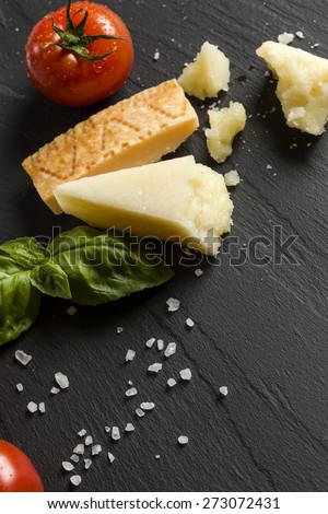 Parmigiano on black background with tomatoes basil and salt - stock photo