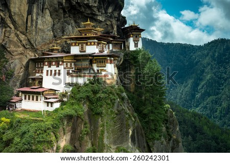 PARO, BHUTAN - AUGUST 11, 2014: Paro Taktsang Monastery is the most famous buddhist temple of Bhutan which clings to a cliff, 3120 meters above the sea level on the upper side of Paro valley, Bhutan. - stock photo