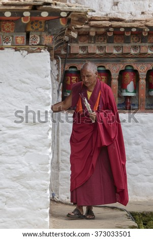 PARO, BHUTAN - CIRCA AUGUST 2014.  Kyichu Lhakhang is the oldest temple in Paro.  Here, a monk practises his faith by turning prayer wheels set in the walls of the monastery