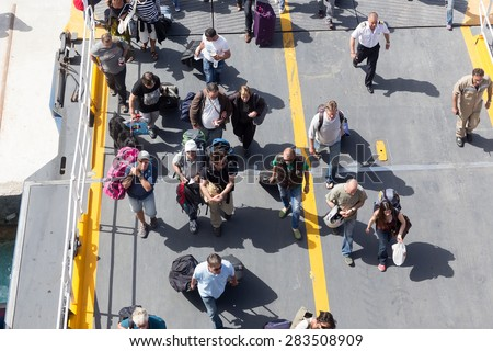 PAROS, GREECE, MAY 17, 2015: Passengers board the ship at the port of Paros in Greece.The Paros is an island in Cyclades that accepts too many tourists every year