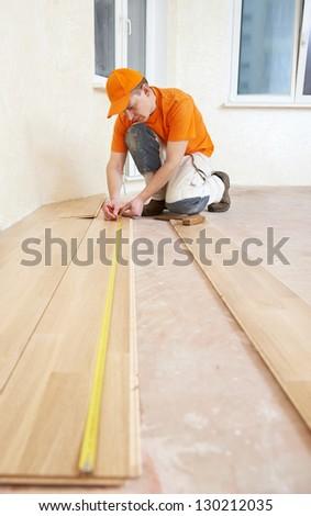 parquet floor layer carpenter worker installing wood parquet board during flooring work - stock photo