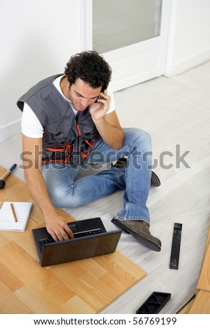 Parquet layer on phone sitting on the floor in front of a laptop computer - stock photo